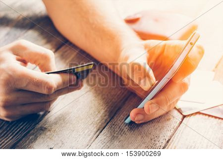 Man Hands holding credit card and using mobile phone in sunlight. Online shopping online banking and online marketing. shallow depth of field toning photo