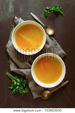 Bouillon or broth served in two bowls on a rustic dark table view from above