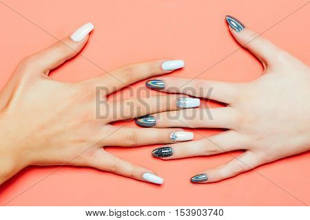 glamour female hands and fingers with fashionable trendy nail polish white and silver colors on fingernails has soft skin of young human on orange background closeup