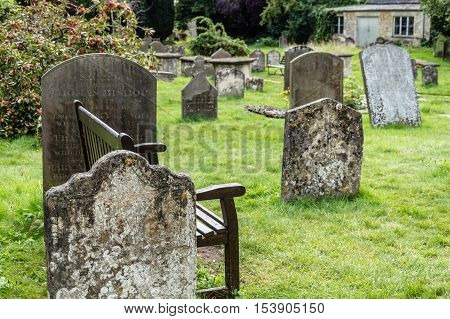 Cirencester UK - August 17 2015: Wooden bench in the churchyard of the Parish Church of St John Baptist in Cirencester.