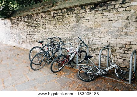 Cirencester UK - August 17 2015: Bicycles parked in a stone wall. The city is a market town in the cotswolds and is known to be an important early Roman area.