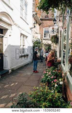 Gloucester UK - August 17 2015: St Colorful alley near Cathedral with tourist and many flowers. Gloucester is an english town near Welsh border founded by the Romans