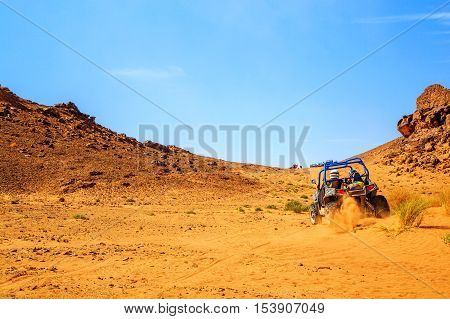 Merzouga Morocco - Feb 26 2016: back view on great canyon with blue Polaris RZR 800 in Morocco desert near Merzouga. Merzouga is famous for its dunes the highest in Morocco.