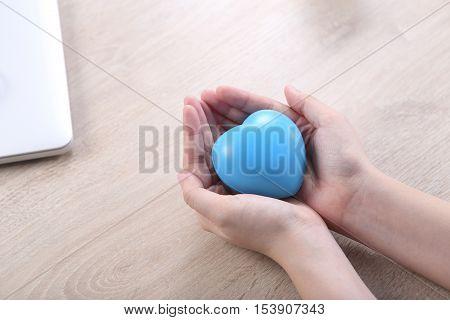 Hand holding ball heart shape on wooden desk