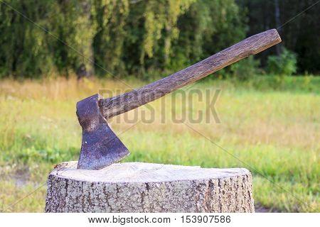 A hatchet on a stump , on a green background.Ax, hatchet, axe.