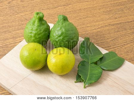 Vegetable and Herb Fresh Kaffir Lime with Persian Lime and Kaffir Leaves for Seasoning in Cooking on A Wooden Board.