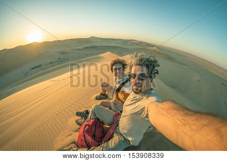 Adult couple taking selfie on sand dunes in the Namib desert Namib Naukluft National Park main travel destination in Namibia Africa. Fisheye view in backlight toned image.