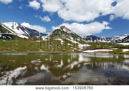Summer landscape of Kamchatka: view of Mountain Range Vachkazhets and clouds in blue sky reflection in mountain lake on sunny day. Eurasia Russian Far East Kamchatka Peninsula.