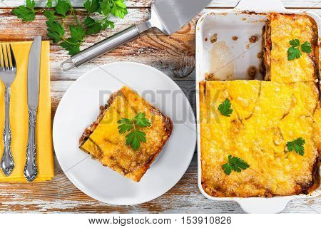 Portion Of Delicious Moussaka On Plate And In Gratin Dish