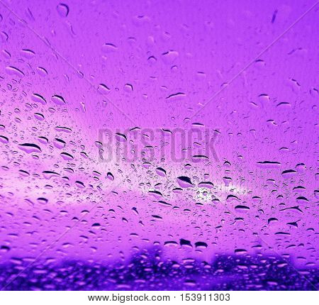 rain drops falling onto glass and tinted sky from mauve to blue.