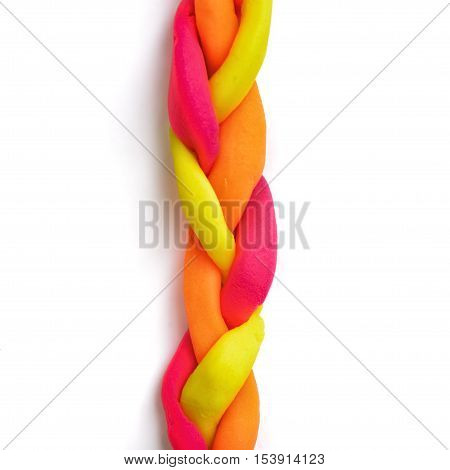 A close-up of a pigtail made of orange, yellow and pink plasticine on the white background. Art and creativity, Games for children. Handmade objects.