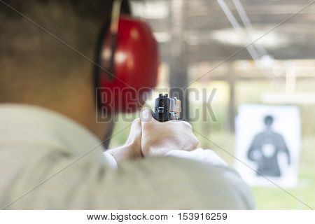 Shooting With Gun At Target In Shooting Range. Man Practicing Fire Pistol Shooting.