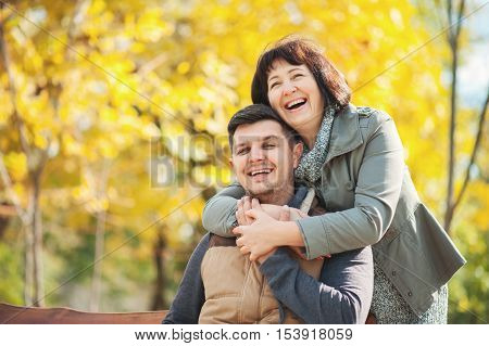 Mature woman with adult son in the autumn park. Happy and smilling