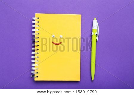 Notebook And Pen With Googly Eyes On A Purple Background