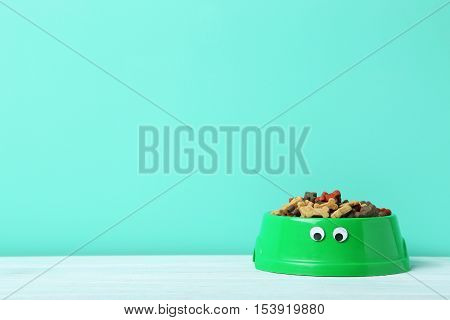 Dog Food In Bowl With Googly Eyes On A Green Background