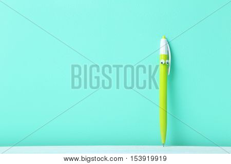 Pen With Googly Eyes On A Green Background