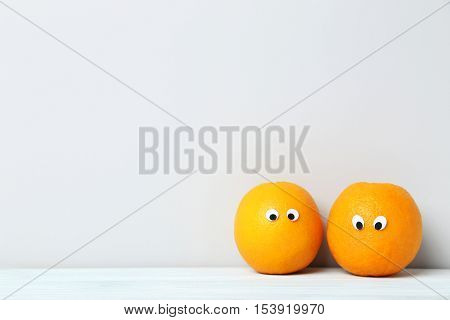 Ripe oranges with googly eyes on grey background