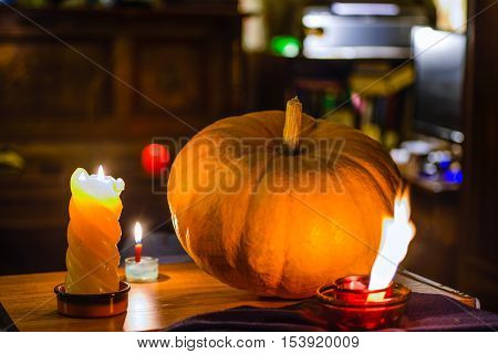 Magic of mystique: a big pumpkin is lit with multiple candles. The blazing fire recalls the image of a horned devil.