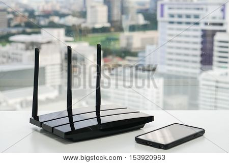 clsoe up black WiFi router with smartphone