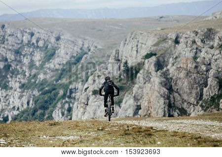 male cyclist on sports mountainbike rides on a mountain trail. view of cliffs