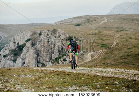 rider cyclists sports mountainbike rides on top of a mountain. Cycling competition mountain bike