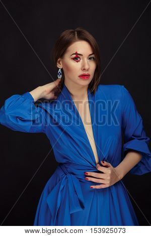 Portrait of a female vampire in a blue dress over black background