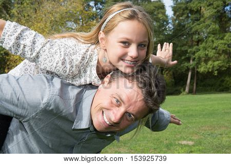 Lovely Father Giving Daughter Piggyback At Park