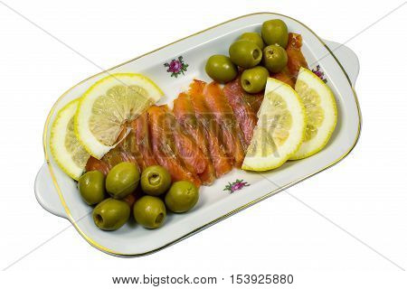 Balyk of a humpback salmon with olives and a lemon isolated on a white background