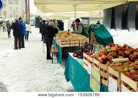MARINER, SLOVENIA - JANUARY 6, 2016: People sells fruit and vegetables at local farmer market in winter Maribor, Slovenia. Selective focus