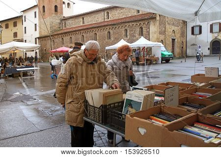PISA, ITALY - JANUARY 9, 2016: People looking around in the second hand book stalls of street flea market in the historical center of Pisa, Italy