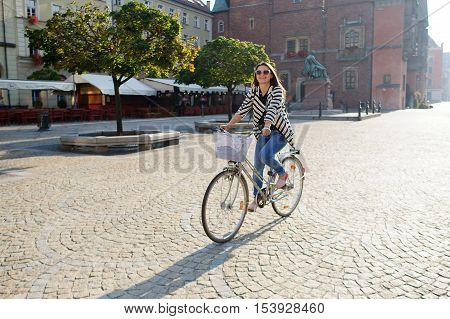Dark-haired young woman in sunglasses rides by bicycle on a paved pavement. Solar morning. Beautiful buildings of the ancient European city a monument green trees. Woman in a good mood she smiles.