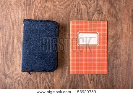 Squared Exercise Book And Pencil Case On Wooden Background