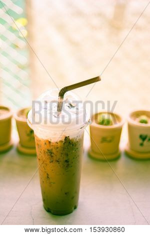 Iced coffee with straw in plastic cup with cuctus backgroundcross process picture style.