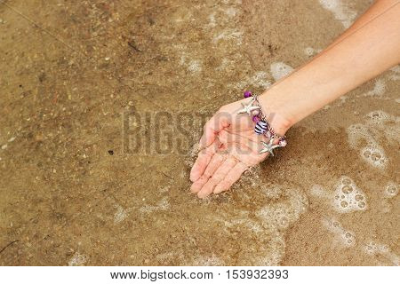 Female hand with a bracelet in the form of seashells closeup scooped up seawater bubbles.