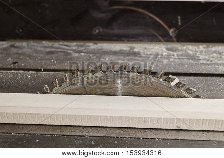 Sawing wooden plate on a workbench in the shift