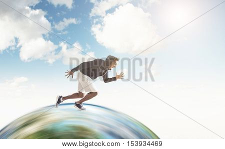 African American guy running on huge globe surface. Concept of the fastest man on Earth. Mock up. Toned image.