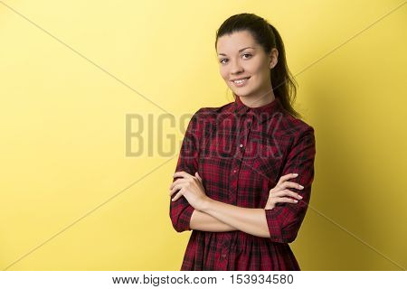 Smiling young woman in red dress standing with her arms crossed against yellow background. Mock up