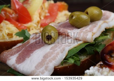 bruschetta with ham olives and arugula, bruschetta with ham bruschetta with cottage cheese and tomatoes on a wooden table