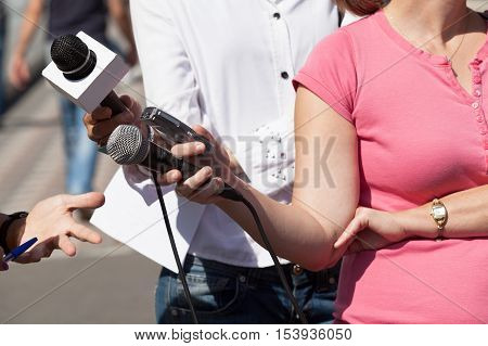 Media interview. Female reporter holding a microphone conducting an TV or radio interview.