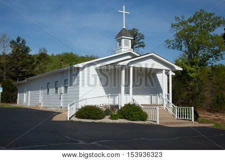 A white country church under a blue sky.