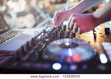 Dj mixes the track in nightclub at party
