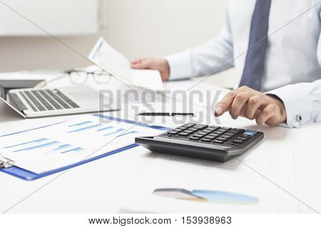 Man Using Calculator And Holding Important Document