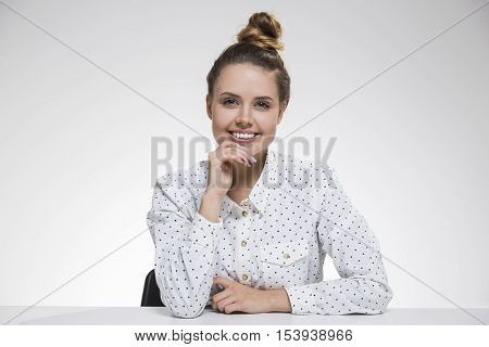 Girl in polka shirt is smiling broadly to the viewer and sitting with her hand on the chin. Concept of tokens of friendliness. Mock up