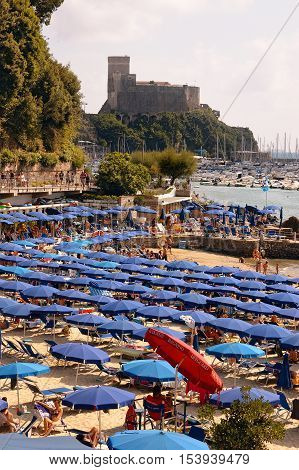 LERICI ITALY - JULY 16 2011: The Lido di Lerici beach crowded with bathers on a sunny day in july. Beach near the village of Lerici in the Gulf of La Spezia Liguria Italy