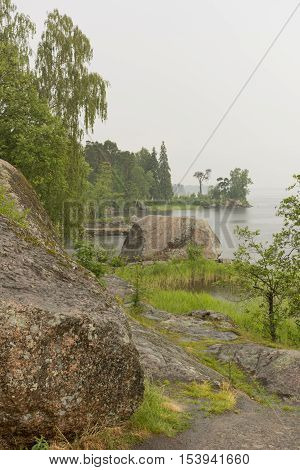 beach with stone boulders bushes green grass and trees on the shore of Protective Gulf of Finland and the mon repos Park Vyborg