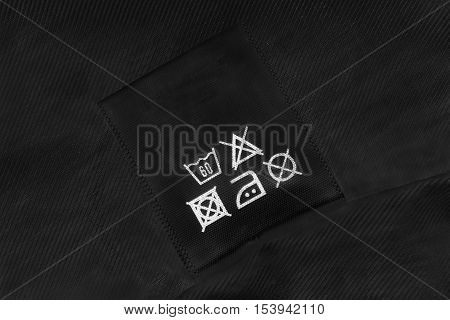 Washing instructions label on black cloth as a background