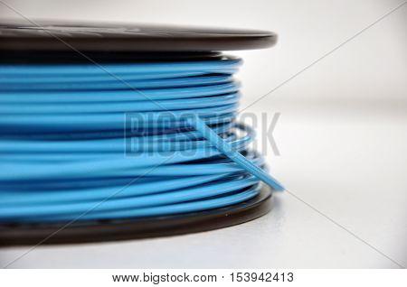 Blue 3d printing filament plastic spool on table