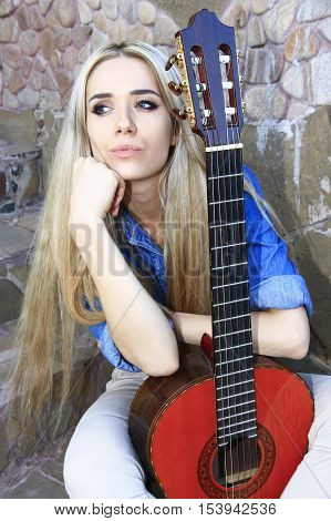 Young beautiful woman holding a Spanish guitar on old wall background.