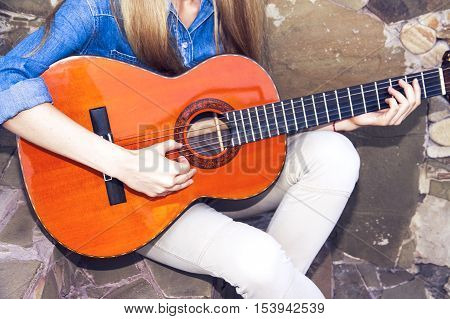 Young beautiful girl playing the Spanish guitar on old wall background.