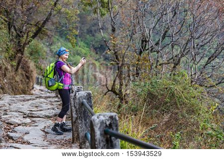 Young hiker tourist taking photo with the smartphone